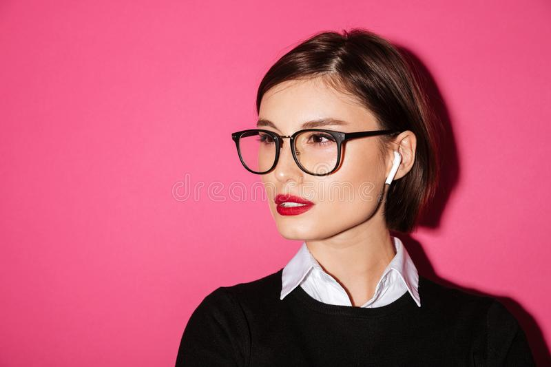 Close up portrait of a confident attractive businesswoman. In eyeglasses looking away at copy space isolated over pink background stock image