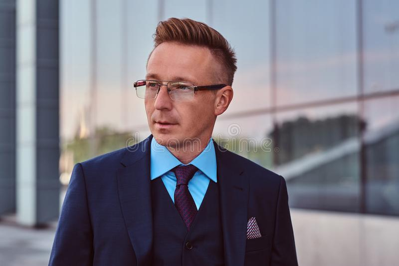 Close-up portrait of a confident stylish businessman dressed in an elegant suit looking away while standing outdoors stock image