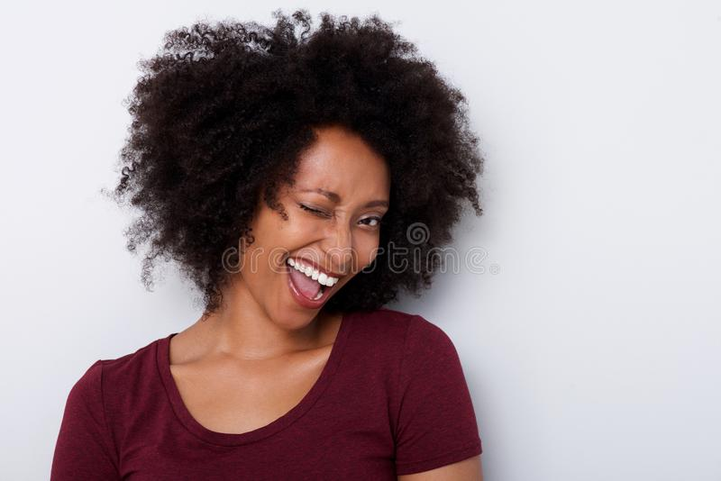 Close up crazy young black woman winking and laughing against white background stock image