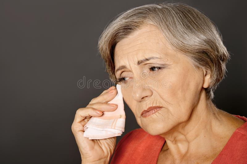 Close up portrait of crying beautiful senior woman  on grey background stock photography
