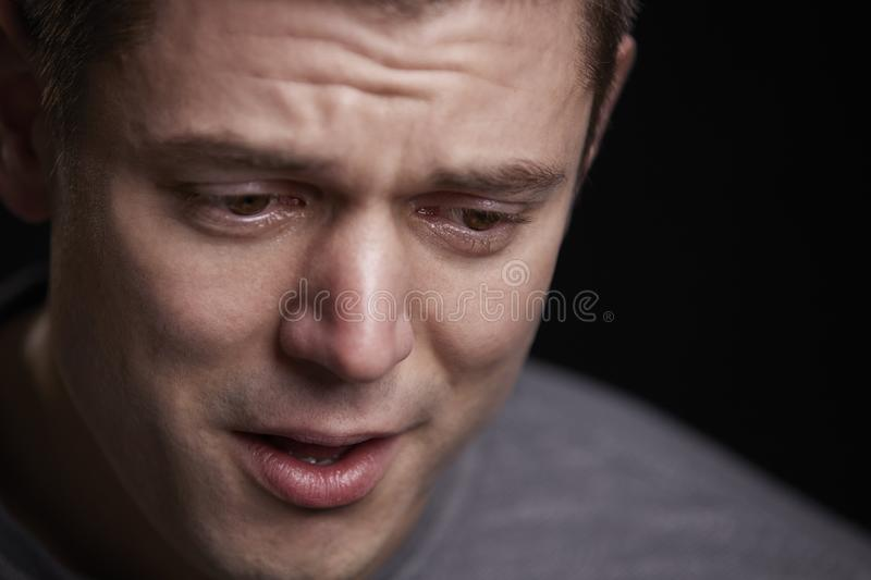 Close up portrait of crying young white man looking down stock photography