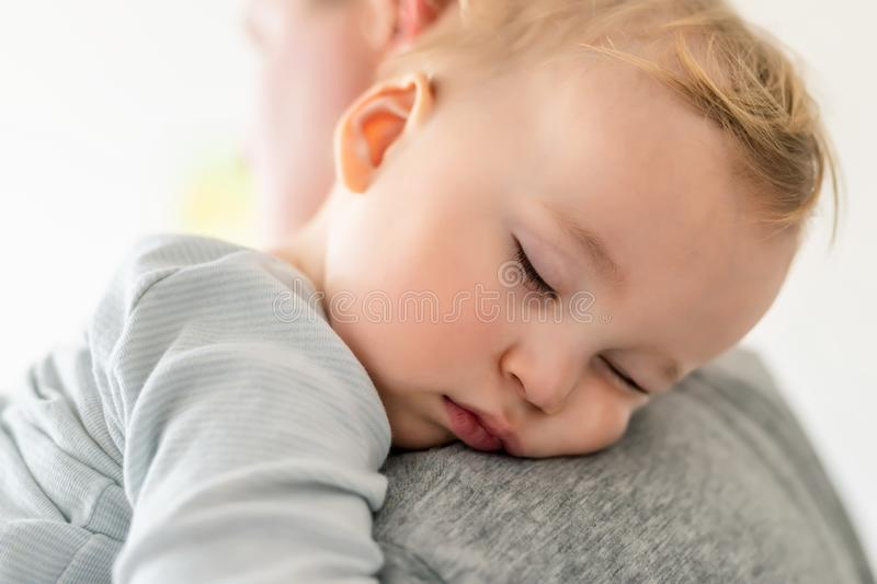 Close-up portrait of cute adorable blond caucasian toddler boy sleeping on fathers shoulder indoors. Sweet little child feeling royalty free stock image