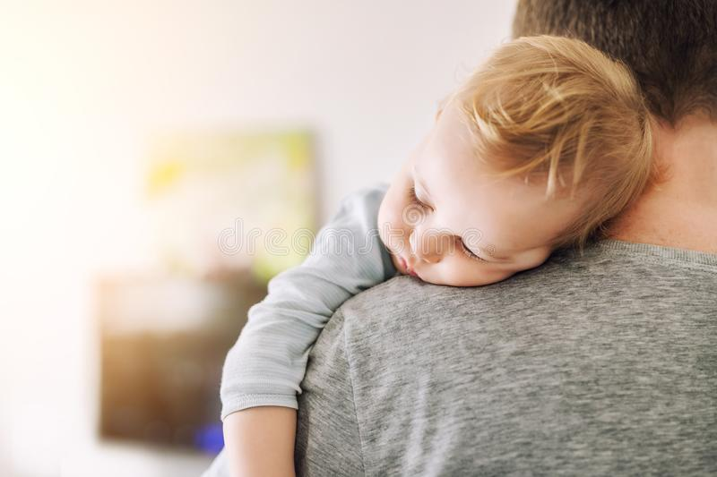 Close-up portrait of cute adorable blond caucasian toddler boy sleeping on fathers shoulder indoors. Sweet little child feeling. Safety daddys hand royalty free stock photo