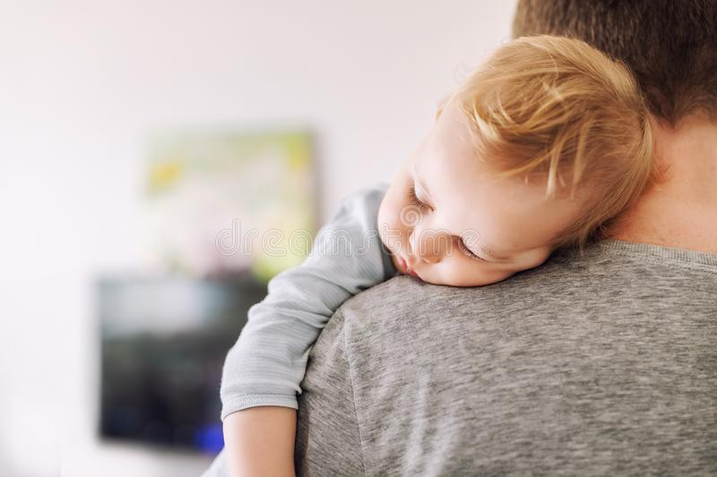 Close-up portrait of cute adorable blond caucasian toddler boy sleeping on fathers shoulder indoors. Sweet little child feeling. Safety daddys hand royalty free stock photos