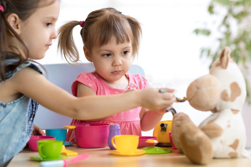 Close-up portrait of cute adorable little kids feeding caw plush toy stock image