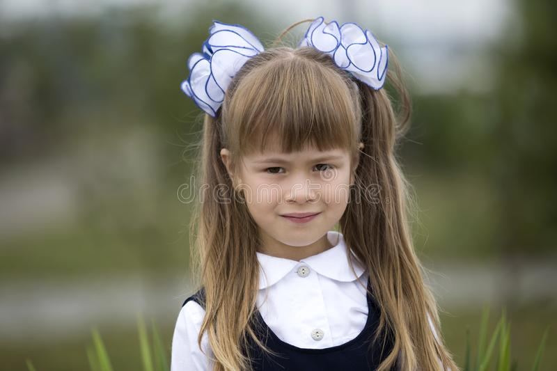 Close-up portrait of cute adorable smiling little first grader girl in school uniform and white bows in long blond hair on blurred royalty free stock photography