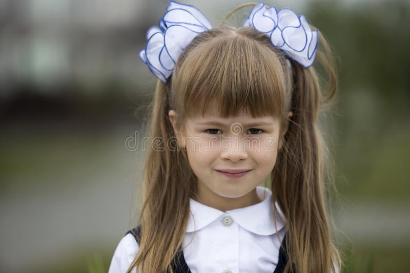 Close-up portrait of cute adorable smiling little first grader girl in school uniform and white bows in long blond hair on blurred royalty free stock photos