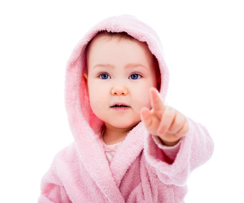 Close up portrait of cute baby girl in pink bathrobe after bath pointing at something isolated on white. Background royalty free stock photo