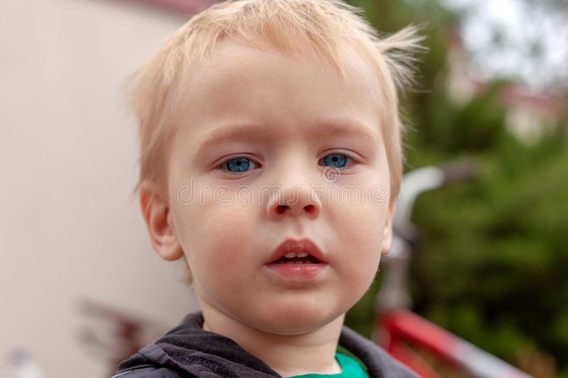 Close up portrait of cute caucasian baby boy with serious expression in blue eyes. Fair hair. Strong emotions. Outdoors, green background, copy space royalty free stock photos