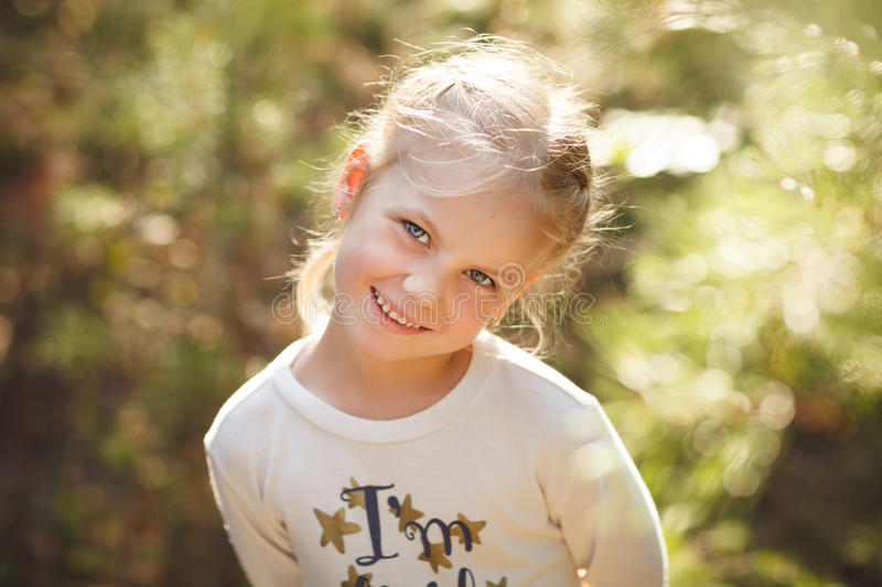 Close-up portrait of cute cheerful little girl in park stock photography