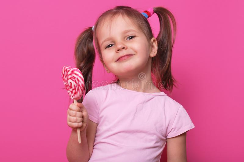 Close up portrait of cute child wearing rose casual t shirt, happy little girl holding big sugar lollipop, has gladness facial stock image