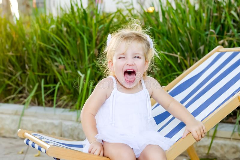 Close up portrait of cute emotional blondy toddler girl in white dress sitting on the deckchair and yelling. City park recreation royalty free stock photos