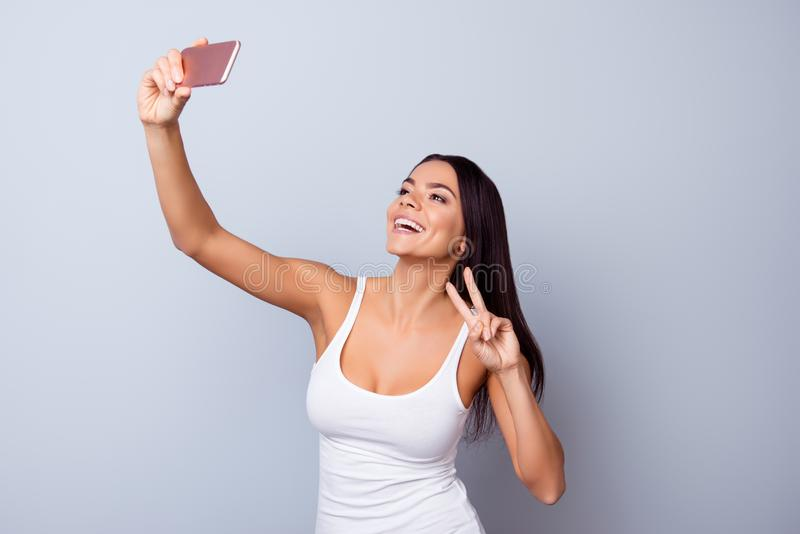 Close up portrait of cute excited latin girl making selfie with stock images
