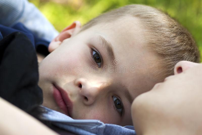 Close-up portrait of cute handsome child boy with gray dreamy eyes outdoors laying on green grass close to mother on warm sunny royalty free stock photo