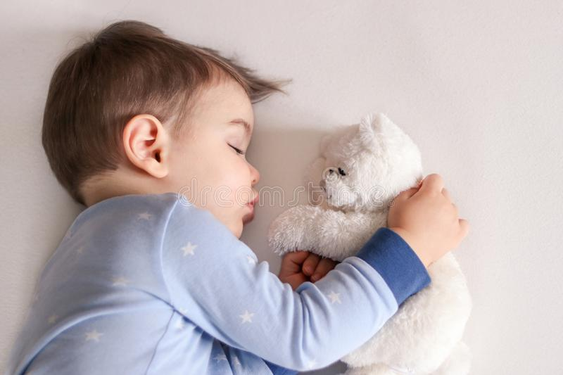 Close up portrait of cute little baby boy in light blue pajamas sleeping peacefully on bed at home hugging white soft teddy bear t. Oy. Child daytime sleeping stock photo