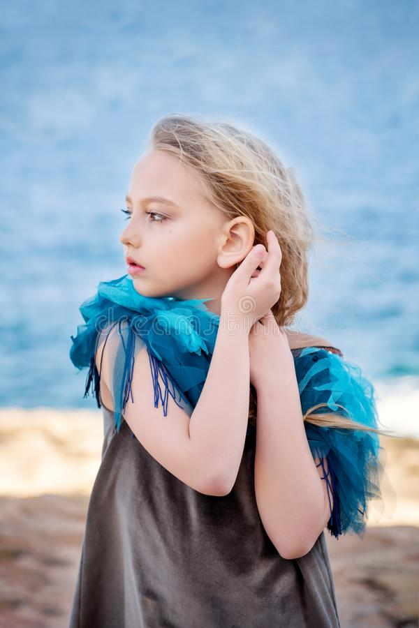 Close-up portrait of a cute little blonde girl staring into the far sea dreamily posing with her hands near her ear royalty free stock image