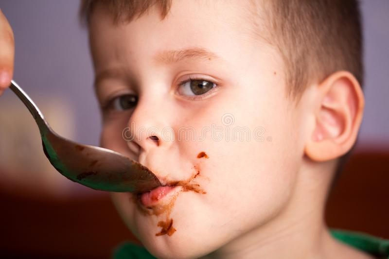 Close up portrait of Cute little boy eating chocolate yogurt at breakfast. Face messy with chocolate and naughty facial expression stock photo