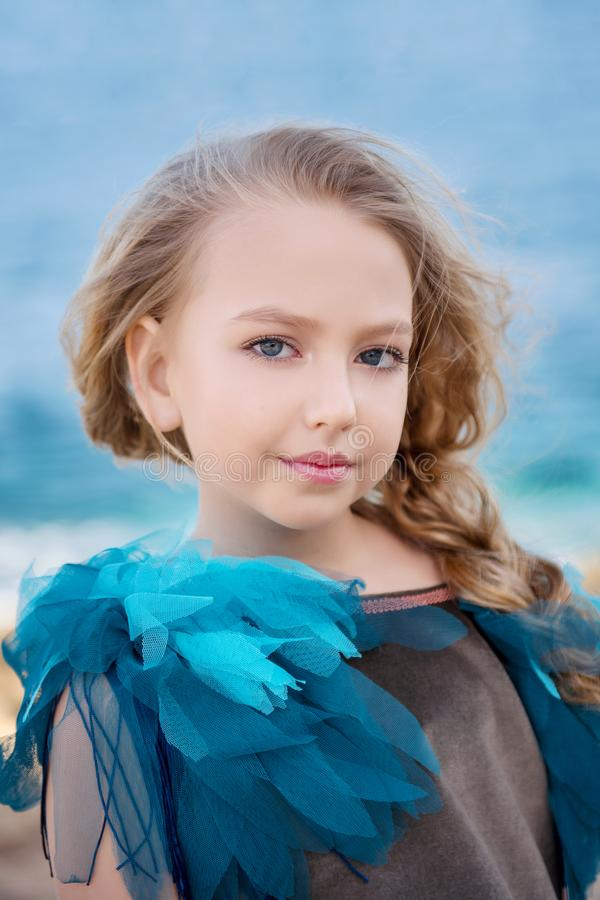 Close-up portrait of a cute little girl with a blond tress on the background of azure sea royalty free stock image