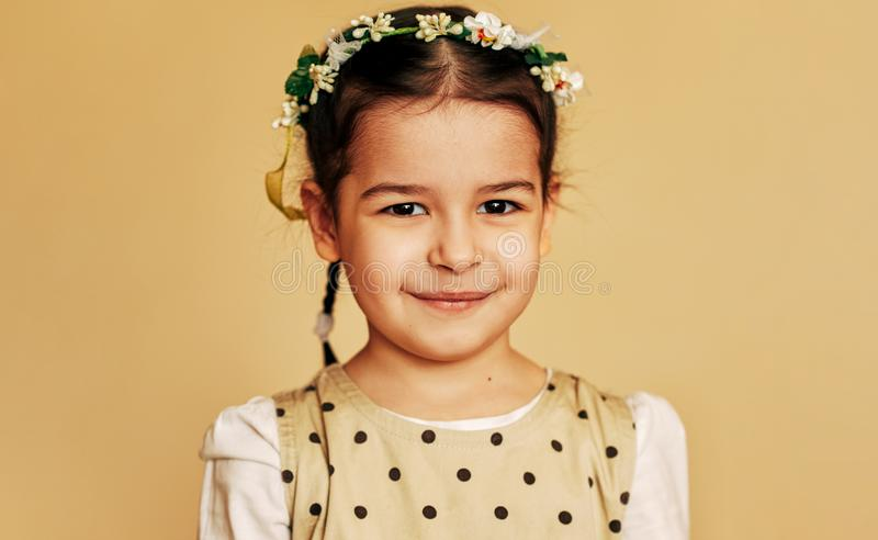Cute little girl with flowers on her hairstyle, looking at the camera with satisfied expression, posing for family photo royalty free stock photos