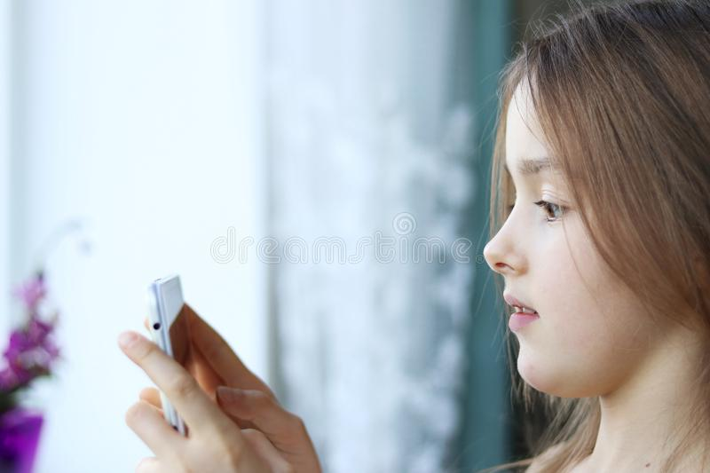 Close up portrait of cute little girl looking at screen of digital tablet or phone with scared surprised face stock image