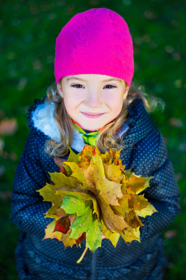 Close up portrait of cute little girl with maple leaves in autum royalty free stock photos