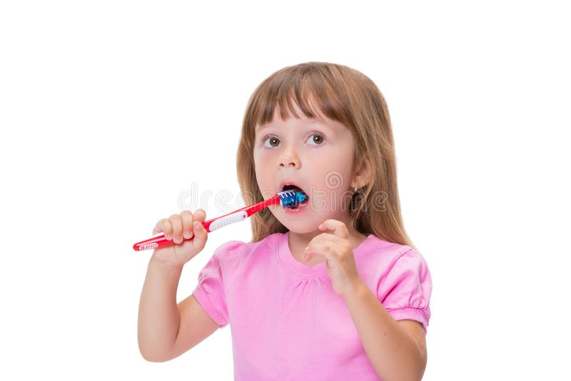 Close-up portrait Cute little girl 3 year old in pink t-shirt brushing her teeth isolated on white background royalty free stock images