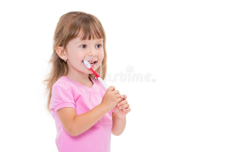Close-up portrait Cute little girl 3 year old in pink t-shirt brushing her teeth isolated on white background stock image