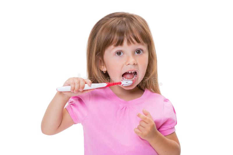Close-up portrait Cute little girl 3 year old in pink t-shirt brushing her teeth isolated on white background stock images