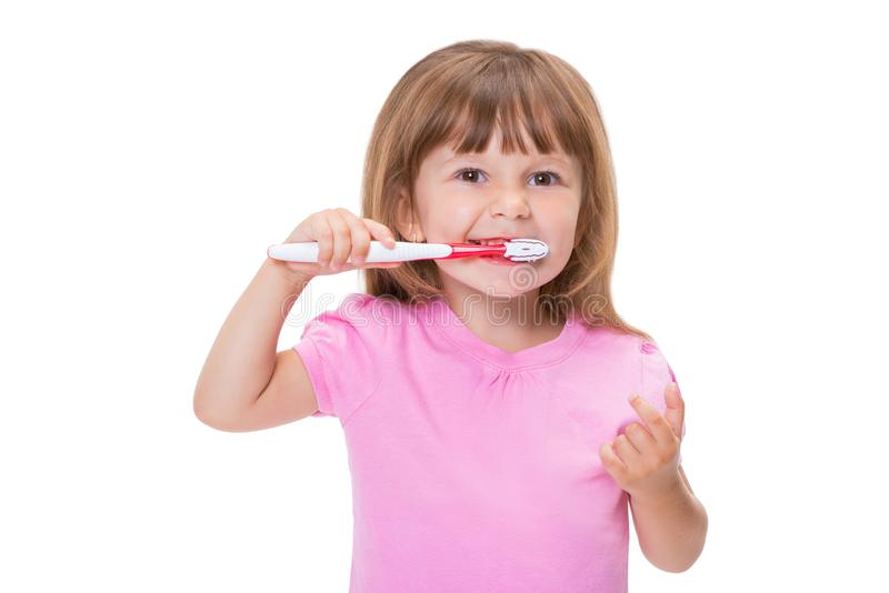Close-up portrait Cute little girl 3 year old in pink t-shirt brushing her teeth isolated on white background stock photo