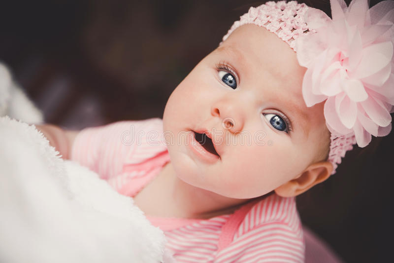 Close-up portrait of cute 3 months old smiling baby girl in pink lying down on a white bed at home. Big open eyes royalty free stock photography