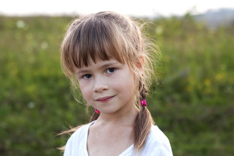 Close-up portrait of cute pretty child girl with gray eyes and long fair hair braids smiling shyly on blurred sunny summer green royalty free stock images