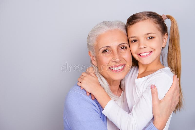 Close up portrait of cute small lovely granddaughter and her charming nice kind granny they are hugging isolated on gray. Background copy-space stock photos
