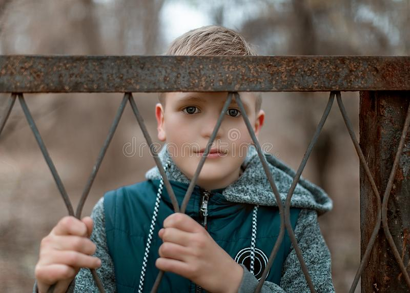 Close-up portrait of a cute teen boy standing behind a metal fence. stock photography