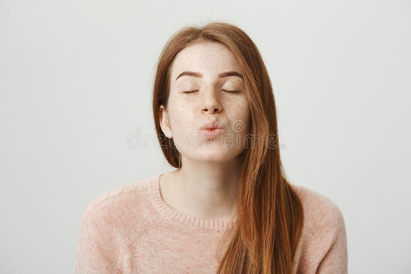 Close-up portrait of cute and tender redhead woman standing with closed eyes and pleased expression, folding lips and stock image