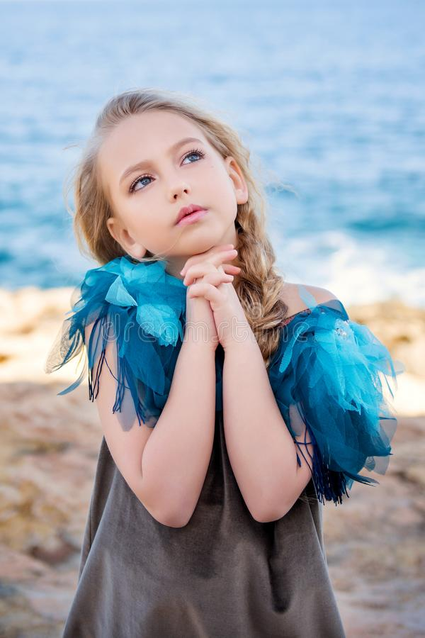 Close-up portrait of a cute young blond girl making a wish with hands clasped in fists in a dreamy pose on the sea royalty free stock photography