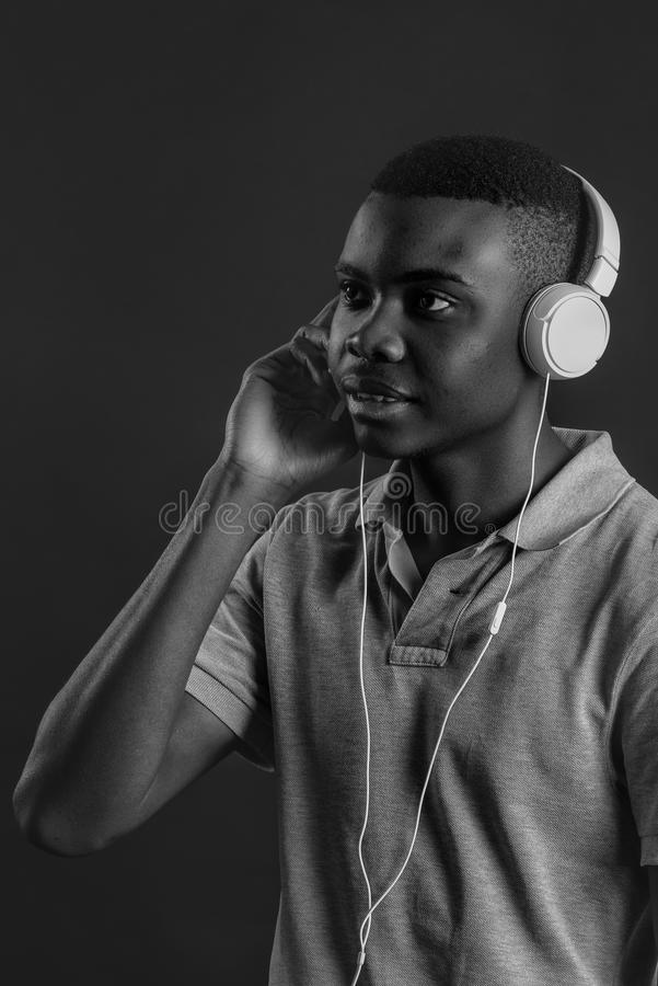 Close up portrait of dark skinned man with closed eyes, has headphones, listens to favourite music. royalty free stock images