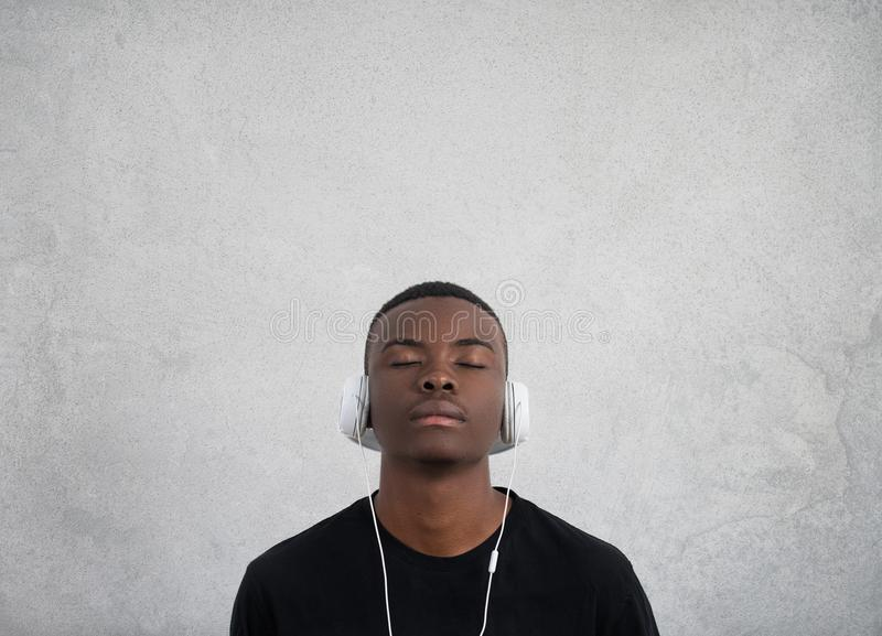 Close up portrait of dark skinned man with closed eyes, has headphones, listens to favourite music. Teenager enjoys stock image