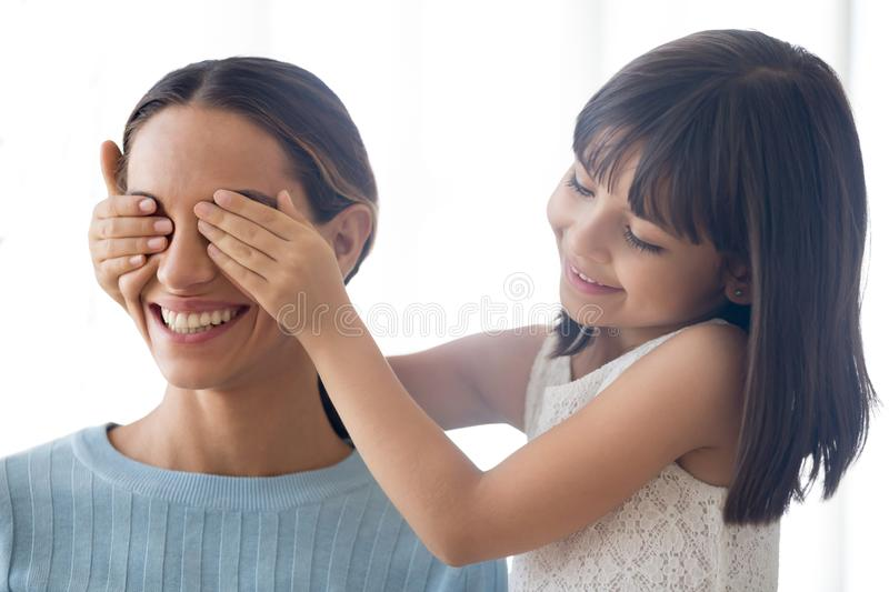 Close up portrait daughter cover mum eyes with hands royalty free stock photo