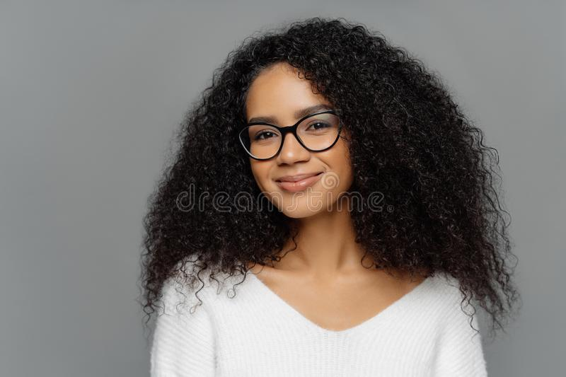 Close up portrait of delighted beautiful Afro woman with bushy curly hair, looks through transparent glasses, wears white sweater stock images