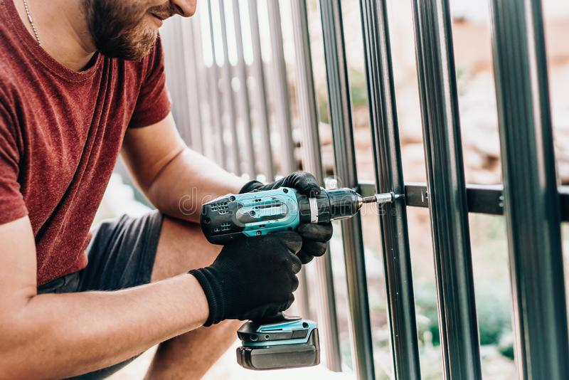 portrait and details of caucasian male worker using screwdriver and screwing metal fence stock images