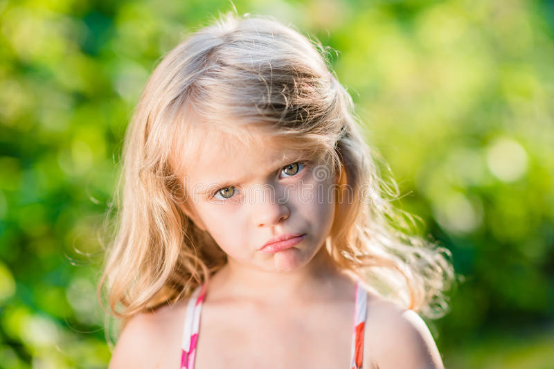 Close-up portrait of displeased little girl with pursed lips. Close-up portrait of displeased blond little girl with pursed lips. Sunny summer day in beautiful royalty free stock photo