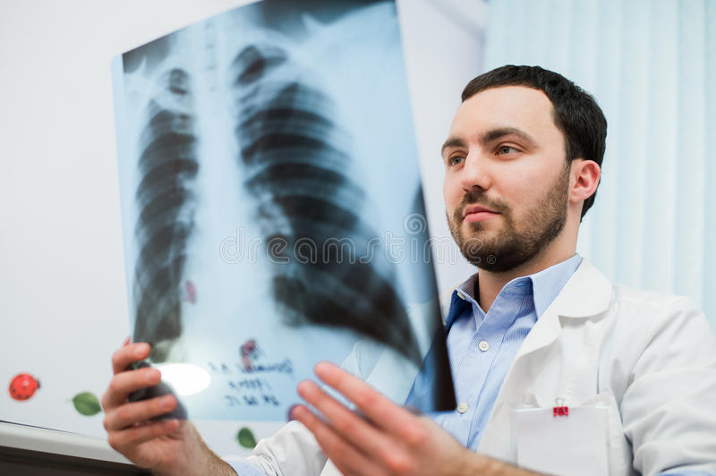 Close up portrait of doctor looking at chest x ray in his office stock photo