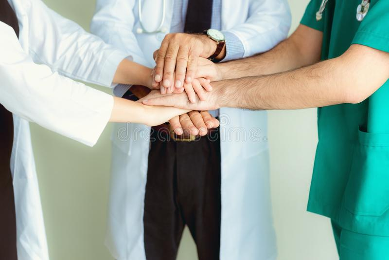Close up portrait of doctors teamwork stacking hands together at stock photography