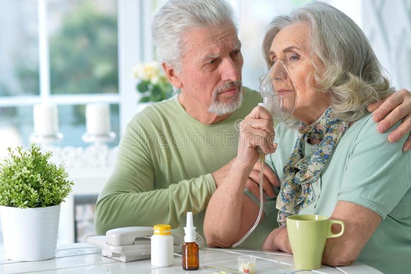 Close-up portrait of an elder couple making inhalation royalty free stock photos