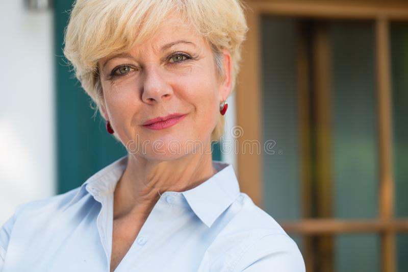 Close-up portrait of an elegant senior woman looking at camera w stock photo
