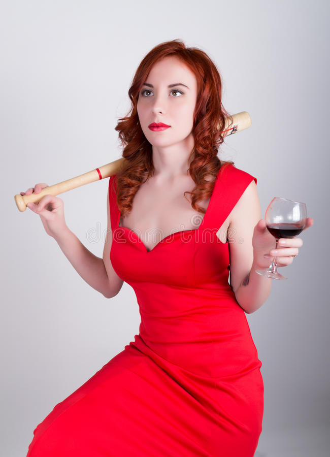 Close-up portrait of Elegant young redhead woman in a red dress, drinking red wine and holding a baseball bat stock images