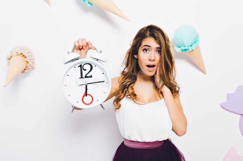 Close-up portrait elegant young woman in stylish dress, posing with white clock on decorated background. Long-haired stock image