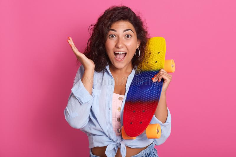 Close up portrait of emotional beautiful female wearing pink top and blue shirt, raising one hand, holding bright skateboard,. Opening her mouth and eyes with royalty free stock images