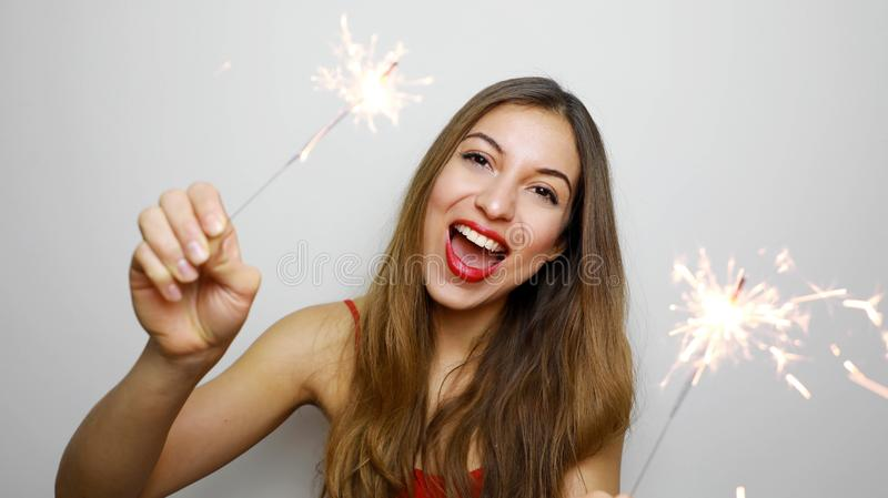 Close-up portrait of emotional female model holding sparklers on white background. Laughing blonde girl in red top posing with. Bengal lights royalty free stock images
