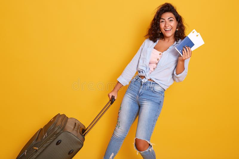 Close up portrait of European Caucaian female dressed in stylish clothes carries suitcase with airplane tickets and documents, stock image
